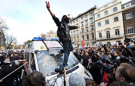 Rejection of authority: Protesters vandalise a police van at anti-austerity protests in 2010