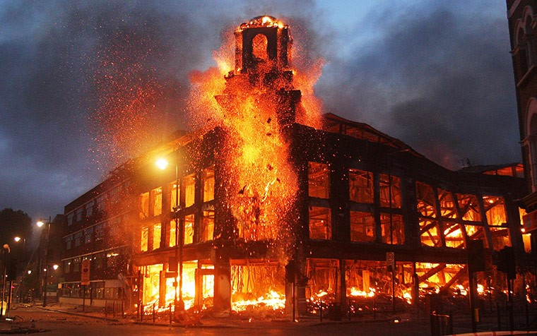 A shop front and flats burn after being set alight by rioters in Tottenham, London in 2011